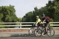Two cyclists riding side by side