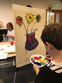 Child doing a painting of a flower vase with vibrant colors