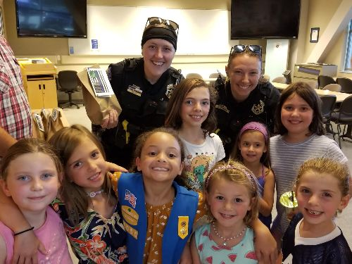 Two female officers with a group of smiling Girl Scouts
