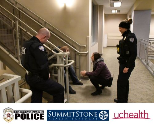Three people kneeling down talking to a distressed person on a stairway.