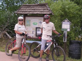 Volunteer ranger assistants on bicycles next to a natural area signpost