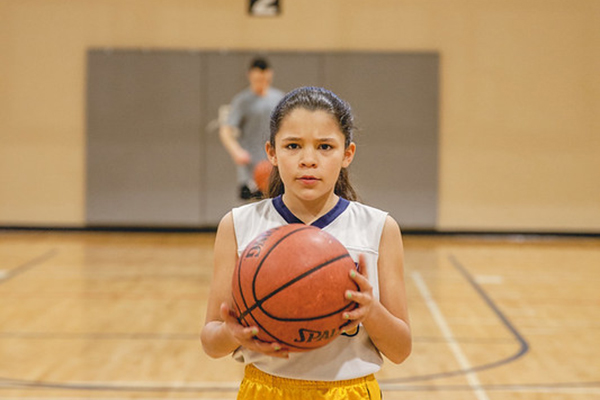 girl holding basketball on court