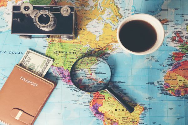 photo of map with camera, passport book and coffee