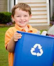 Young boy holding a recycling bin