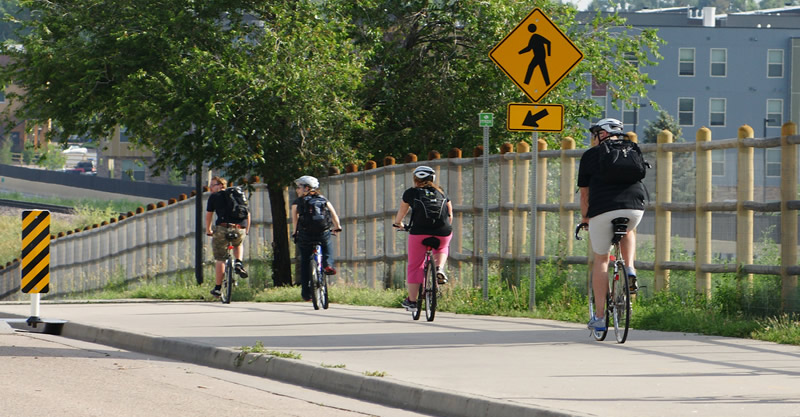 Four people riding bicycles on a bridge